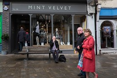 Disapproval (Silver Machine) Tags: winchester hampshire streetphotography street candid candideyecontact man sitting bench smoking couple walking frown outdoor people mintvelvet fujifilm fujifilmxt10 fujinonxf18mmf2r