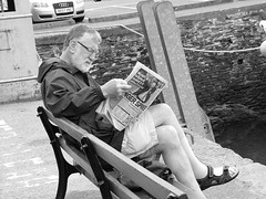 Newspaper, Shorts And Sandals.... (Fire*Sprite*75) Tags: street blackandwhite man bench reading glasses newspaper dock cornwall sitting sandals shorts padstow quayside