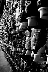 Hockey Skates (Jade Chanoquaway) Tags: nikon nikkor d5500 blackandwhite black white grey gray grayscale greyscale bw contrast light shadow monochrome silhouette shadows vanishing perspective rows rack racks metal blades blade boot boots lace laces inside display store hockey hockeyskate hockeyskates skate skates skating texture pattern september canada ontario sport sports sporting sportinggoods