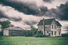 Are We In Kansas? (CJ Schmit) Tags: wwwcjschmitcom 5dmarkiii canon canon5dmarkiii cjschmit cjschmitphotography tamron70200mmf28dildifmacroaf photographermilwaukee milwaukeephotographer photographerwisconsin wisconsin fonddulac farm country grass house farmhouse barn trees summer clouds decay rundown chimney antenna nikanalogefex2 stormy overcast grey gloomy rural ruins