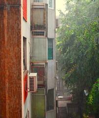 Technicolor against the shower (mi ne volimo alu) Tags: rain asymmetry architecture absence beograd citylife foliage geometry green building skyscraper window shower gloom orange terracote perspective urban view