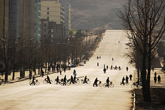 PRK-Kaesong-0811-16-v1 (anthonyasael) Tags: road street trees people urban sunlight man building tree men bicycle horizontal architecture buildings walking person one 1 streetlight uniform asia crossing adult bright streetlamp walk rear transport fulllength places korea east roads fareast adultsonly northkorea eastasia dprk prk urbanscene backgroundpeople kaesong buildingexterior onemanonly peopleinthebackground backgroundperson anthonyasael fareastasia democraticrepublicofnorthkorea