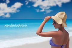 Gazing (Kordelakos) Tags: sea summer sky woman hat clouds emptiness calmness