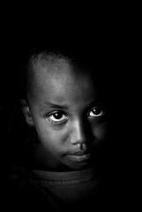 Child portrait (Ethiopia) (Josep Castell) Tags: world poverty city travel viaje light shadow portrait people bw white black guy eye blanco luz face dark children ojo photography photo calle eyes village child gente outdoor retrato sony flash pueblo culture photojournalism dramatic lifestyle ciudad social nios ojos 200 reflejo quarter chico ethiopia alpha nio mundo cultura joven pobreza oscuro fotografa etiopia fotoperiodismo