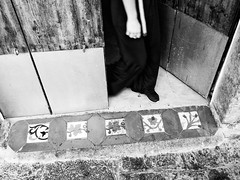 A Foot In The Door (Pablo Germade) Tags: streetphotography urban people person door foot step mano hand pie paso puerta umbral tiles mosaic mosaico azulejos home hogar casa house woman mujer byn bw blancoynegro blackandwhite pablogermade olympus omd em5 eivissa ibiza spain espaa