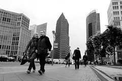 Walking in Potsdamer Platz (Gianluca De Simone) Tags: berlin street photography photo rapid shot people walking potsdamer platz palace germany black white bw car mister happy smile