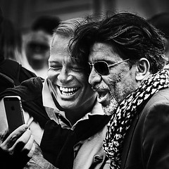 That must be funny.  (D80_452075 - 1) (Itzick) Tags: denmark copenhagen twopeople faces smiling smile candid d800 itzick streetphotography cellphone shades