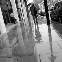 Rainy days (Spannarama) Tags: uk blackandwhite man london wet rain umbrella reflections square rainy bunhillrow ec1 wetpavement