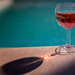 Glass of rosé wine on the side of the pool