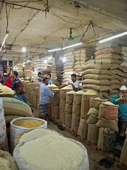 Do you need some rice? We have a dozen types! (karla.hovde) Tags: bangladesh asia travel dhaka city urban rice men people market bazar shop repetition pattern bags sacks stacks food indoor