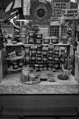 Riga - Central Market Honey Stall (Nicholas Olesen Photography) Tags: riga latvia market blackandwhite monochrome indoors central europe vertical person woman stall vendor commerce selling honey travel tourism nikon d90