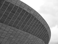 Velodrome, London (B/W) (DaveJC90) Tags: park new uk greatbritain blue light sky blackandwhite bw cloud sun sunlight white black game colour detail building london modern night dark logo evening design athletics colours bright unitedkingdom britain stadium sunny shoppingcentre games sharp event crop british olympic olympics athlete olympicstadium olympicpark velodrome stratford 2012 olympicgames london2012 croped sharpness teamgb aquaticscentre theorbit