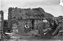 Mountain Stage, Glenbeigh, Co. Kerry (National Library of Ireland on The Commons) Tags: robertfrench williamlawrence lawrencecollection lawrencephotographicstudio thelawrencephotographcollection glassnegative nationallibraryofireland cabin stone sods earth squalor congestion poverty turf basket cuttingtools shovel thatch countykerry glenbeigh mountainstage scarf turfspade explore