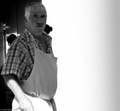 le boucher. (Neil. Moralee) Tags: franceneilmoralee neilmoralee boucher butcher man meat work working bright brite shadow old mature french candid neil moralee nikon d7100 portrait black white blackandwhite bw mono monochrome contrast sunshine food market village shop shopping apron butchery