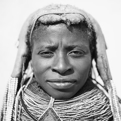 Mwila Woman With Vilanda Necklace At Huila Town Market, Angola (Eric Lafforgue) Tags: africa portrait people blackandwhite woman face dreadlocks female square person one necklace beads exterior head tribal headshot ornament braids tribe humanbeing plaits oneperson huila angola southernafrica mwela lookingatcamera squarepicture ethnicgroup traditionalhairstyle vilanda mumuhuila mwila southangola mumuhuilatribe mwilatribe nontombi vilandanecklace mudnecklace ango01448