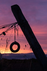 The leaning pole and the fishing net (ice-cold photography) Tags: sunset red orange net circle fishing fisherman village purple calm pole seashore tranquil midnightsun skagastrnd