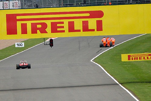 A Ferrari closes on a group of Marshals pushing Charles Pic's Marussia