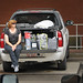 A mom waits patiently at the family truck as she waits for her student to return for the next load of stuff for the dorm room.