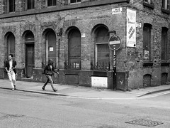 Northern Quarter #115 (Peter.Bartlett) Tags: manchester urbanarte niksilverefex wall walking window unitedkingdom noiretblanc people city facade doorway streetphotography smoking cigarette cellphone olympuspenf peterbartlett man urban monochrome candid uk m43 microfourthirds mobilephone bw doubleyellowlines sign blackandwhite door men