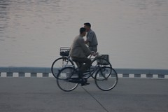 passing by (diminoc) Tags: bicycles pyongyang northkorea dprk boulevard streetphotography grey people riding bike river cycle cycling
