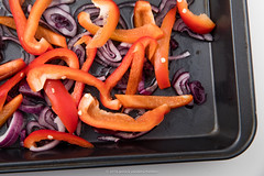 Mix of olive oil, sliced red onion and sliced bell pepper in black baking pan. Step in order to prepare gratin. (annick vanderschelden) Tags: humanhand slice bellpepper redonion pieces gratin cooking baking oven food culinary cuisine preparation slices chopped pointofview