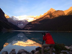 Early morning ritual at Lake Louise (peggyhr) Tags: camera morning blue trees red sky brown sunlight white lake snow canada ice water sunrise reflections grey golden photographer shadows tripod glacier alberta lakelouise taupe canadianrockies victoriaglacier finegold thegalaxy 25faves peggyhr artepuro 100commentgroup dragonflyawards artwithoutend blinkagain photohobbylevel1 thegalaxyhalloffame bestofblinkwinners photohobbylevel2 photohobbylevel3 blinksuperstars supersixstage1~flickrbronze