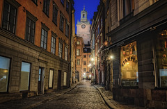 Great Church Alley (henriksundholm.com) Tags: storkyrkan church clock tower steeple oldtown gamlastan stampen windows cobblestone street road pavement sidewalk door dusk night stone city urban old history historical flag lamps lights reflections shadows dark hdr stockholm sverige sweden shops stores st nicholas churchofstnicholas narrow historic
