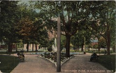 Front: Bronson Park, Kalamazoo, Mich (kplcommons) Tags: kalamazoopubliclibrary sidewalk bronson park fountain outside trees bench people postcard buildings