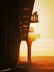Shooting the Breeze (Steve Taylor (Photography) Internet V slow) Tags: ocean sea newzealand christchurch orange silhouette yellow lady sunrise gold dawn pier glow photographer pacific jetty columns canterbury nz southisland sunup newbrighton supports shootingthebreeze