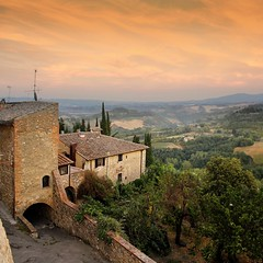 Encircled city wall of San Gimignano at dusk (B℮n) Tags: old city sunset red summer sky italy panorama orange sunlight house colour colors wall fairytale landscape high topf50 artist italia day glow berries estate heart wine cloudy small hill inspired dry ground unesco hills vineyards valley tuscany grapes villa chianti vista strong layers cypress summertime wildflowers taste roads sangimignano middle product viewpoint topf100 ages fruity rubby vino tuscan cultivated hillsides harmonious 100faves 50faves provinceofsiena