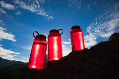 Water Bottles Backlit by Rising Sun in Olympic National Park (Lee Rentz) Tags: blue red sky usa nature water america bottle northwest bottles olympicpeninsula gear plastic equipment pacificnorthwest northamerica translucent backlit seethrough wilderness transparent nalgene washingtonstate olympicnationalpark waterbottle backlighting olympicmountains washingon royalbasin subalpine bpafree