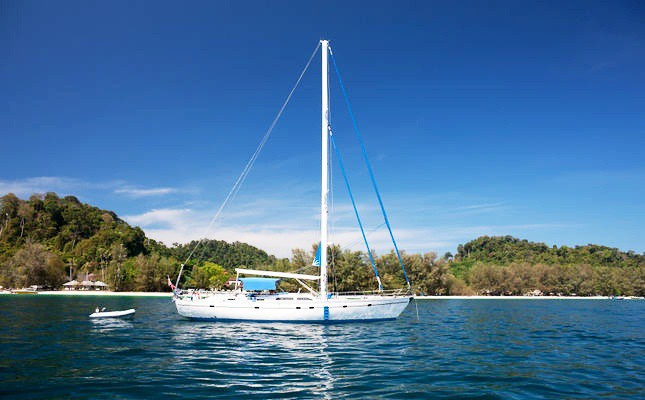 Motor yacht/Sailing boat moored by a tropical island