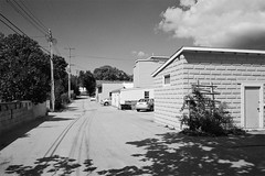 Back Alley, Suttons Bay, MI, 2012 (Tom Powell) Tags: blackandwhite film zeiss vanishingpoint shadows michigan suttonsbay kodakbw400cn 2012 leelanau contaxg2 colornegative 28mmf28biogon
