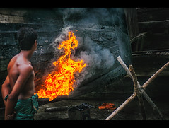 A boat in the making. (Shutterfreak ☮) Tags: street wood people man rural island fire boat construction nikon candid smoke documentary lifestyle bamboo islander maker 70300mm dip bangladesh tar hasin dwip d5000 nijhum inkiad