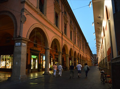 Homeward bound (angelsgermain) Tags: street archway columns arches sky buildings perspective evening people walkers summer shops lights bologna emiliaromagna italia italy