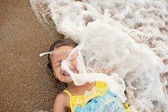 wipe out! (Kelly West Mars) Tags: ocean summer portrait beach water girl smile 50mm sand child play f14 candid lifestyle wave naturallight splash fortstory nikond700