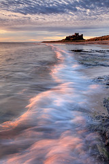 Bamburgh Castle (rgarrigus) Tags: ocean summer england castle water sunrise landscape coast surf shoreline wave medieval september northumberland shore coastline bamburgh goldenhour greatphotographers garrigus robertgarrigus robertgarrigusphotography