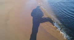 Selfie on the beach of the Elbe River. My right leg was not swallowed by the waves, it stood on a large boulder. You cant see it because of the long shadows. (detlefgabriel17) Tags: selfie shadow schatten wellen waves reflections reflectionen beach strand sand wasser water