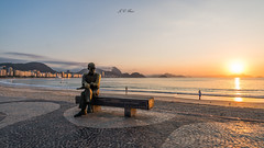 In the land of poets | Sunrise | Copacabana beach (Jos Eduardo Nucci) Tags: sunrise brazil riodejaneiro copacabana carlosdrummonddeandrade statue morning sun beach beautiful sugarloaf southamerica niteri seascape flickr peace landscape joseduardonucci promenade sunlight landmark postcard seasons tropical atmosphere nikon d800 nikkor 1424mm nature icon classic architecture favorite instagram arpoador explore rio450anos wonderfulcity stunning water sea botafogo colors orange blue sky yellow backlight shadow reflection serenity mountains mood tide ocean like love