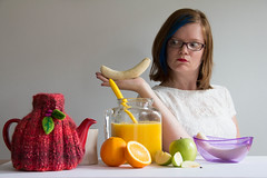 WHAT DID YOU SAY TO ME?!? (lacygentlywaftingcurtains) Tags: fruit pride rainbow spectrum colourful orangejuice teapot oranges apples bananas mug white selfportrait bluehair bluestreak fun redhead redhair woman female people glasses silly ridiculous offendedbyabanana