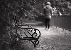 Alone_c (gnarlydog) Tags: monochrome blackandwhite urban streetphotography bench austria cosmicar50mmf14 swirly vintagelens manualfocus shallowdepthoffield emotions walking walkway path detail subjectisolation