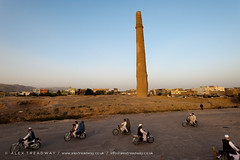 A minaret in Herat (Alex Treadway) Tags: road old city people afghanistan colour building brick tower history archaeology vertical horizontal architecture asian outdoors photography town high ancient asia day traffic minaret islam religion transport middleeast citylife bikes bluesky historic direction pollution afghan civilization column copyspace delicate centralasia fragile motorbikes herat traveldestinations buildingexterior placeofinterest ancientcivilisation indiansubcontinent elevatedview mohammedzahirshah historicbuiding