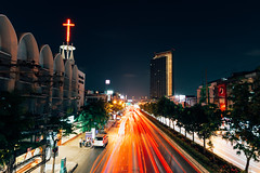 The traffic light trails on the street of Bangkok (Evgeny Ermakov) Tags: life road above city longexposure travel light red urban trafficlights building tower cars tourism church colors car skyline night buildings landscape asian thailand religious lights evening asia southeastasia long exposure cityscape view cross traffic god bangkok religion lighttrails christianity southeast typical effect touristic cartrails christiancross editorialuse