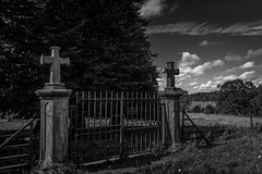 Gateway. (Ian Emerson (Looking forward to a Scotland trip)) Tags: gates ironwork iron stonework stone cross church churchyard clouds trees fence calke canon 1018mm blackwhite heritage nationaltrust