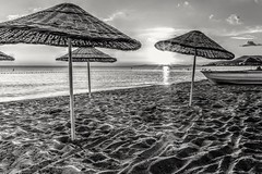 The Empty Beach (Anthony Plancherel) Tags: boat category erdek places seascape sunset time transport travel turkey beach sand parasol sea bay water waves blackandwhite bw whiteandblack monochrome travelphotography landscapephotography ripples canon canon1585mm canon70d outdoor outside outdoors marmarasea turkiye evening shadow shades patterns grains clouds