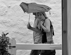 Passing by (farwest56) Tags: street door uk travel england people blackandwhite bw woman holiday man building rain umbrella 50mm mono gate couple cornwall sony cottage tourists stives digy a350 sal50f14
