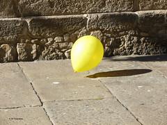 Escapando de la feria. Escaping from the fair. (Esetoscano) Tags: globo balloon amarillo yellow sol sombra calle street piedras stones pavimento pavement ferias fairs