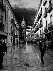 A day of contrasts (Neil. Moralee) Tags: salamanca spain buildings street candid showers rain sunshine contrast people umberella sky dark clouds reflection black white mono monochrome blackandwhite bw neil moralee nikon d7100 architecture tower road walk wet storm man