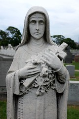 Somber (pburka) Tags: calvary cemetery queens nyc statue sclupture cross catholic rosary veil stone sculpture grave crucifix symbols figure flowers face stare staring