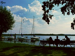 three (Ryuu) Tags: lake silhouettes people candid yachts water landscape green grass blue sky clouds dark silhouette man women 3 three boats lines lightbulb white trees composition bikes bicycles bench sitting shadows turquoise freshair yachting marine sailingboats fz200
